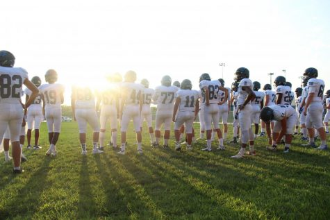 Olathe West Freshman football team gathers together to warm up for their first scrimmage of the year at an event called Friday Night Lights. True the name, the sun light set over them as they prepared for their big night.   Caption: Cache Goracke
