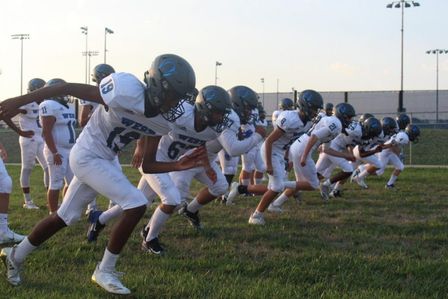 The freshman football team warm up for the upcoming scrimmage.