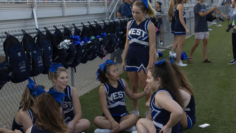 The Cheerleading Team relaxes before their big performance at Friday Night Lights Aug. 24.  Caption: Abi Cantu