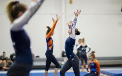 Olathe West Varsity Gymnastics team warms up alongside Olathe East's team before their performance on Sept.13. While Olathe East and Olathe West share a coach, they also compete against one another.