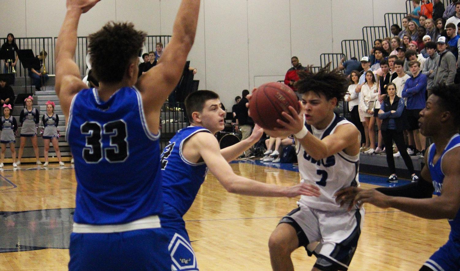 Junior Cougar Downing drives the ball towards the hoop during the Owls losing game.