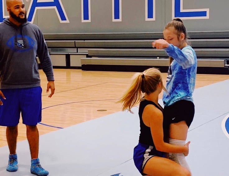 Wrestling coach, Lucas Vincent, coaches two athletes during Summer wrestling camp