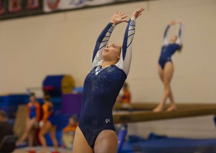 Junior+Makenzie+Juneau+stretches+to+prepare+for+her+performance+on+the+balance+beam.