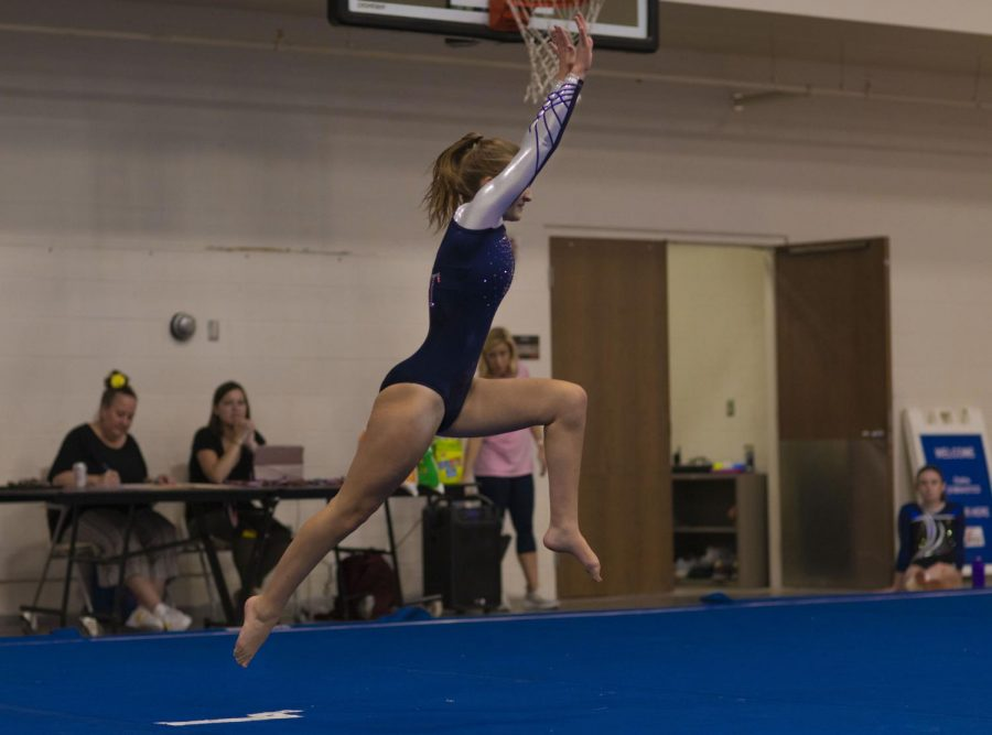 Junior Ava Huntoon springs into the air as the judges, announcers and other team mates watch from the sidelines.
