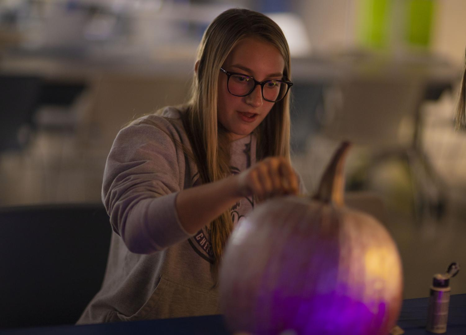 Sophomore Kaitlyn McDonald focuses in on her pumpkin at the Oct. 26 pumpkin painting party for the JV Cheerleaders.
