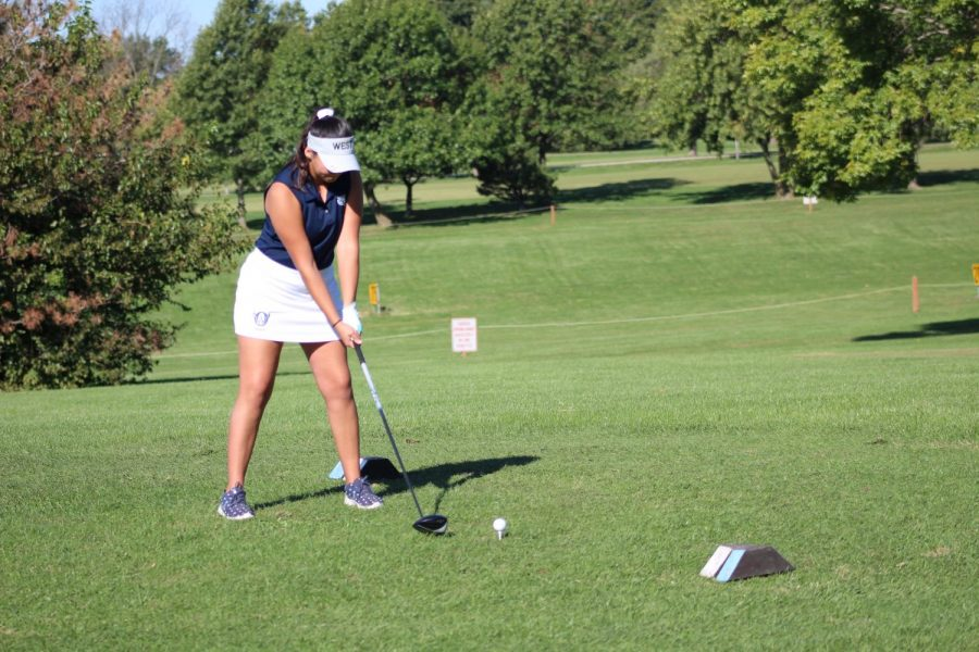 Junior Bailey Basham practices her swing before she tees off on the first hole.