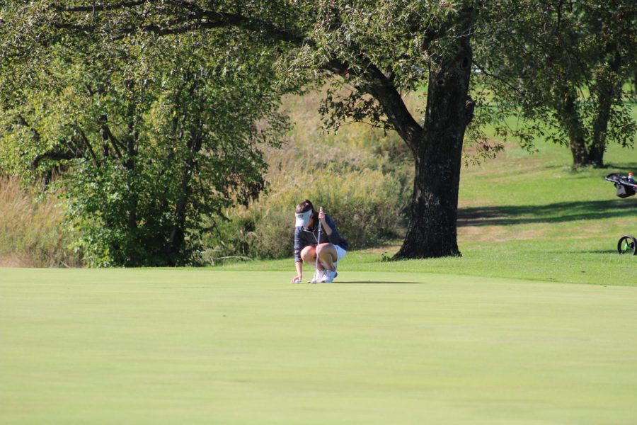 Freshman Liz Lyons lines up her ball to putt on the first hole of the course.