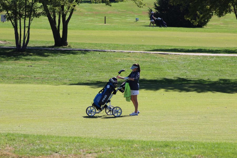 Lyons puts away her clubs and gets ready to walk to the next hole.