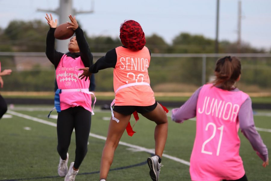 Junior Alyssa Moore jumps to catch a ball thrown during the first half of the Powder puff game on Thursday Oct.3.