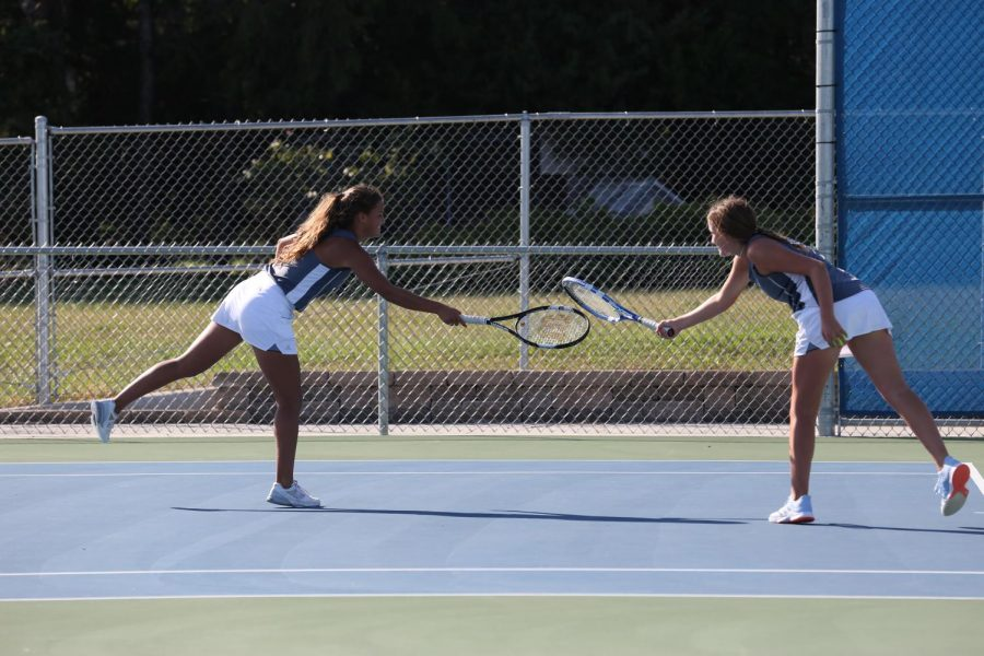 Senior Isabelle Yanes and junior Megan Geyer hit rackets to celebrate a point made in the game.