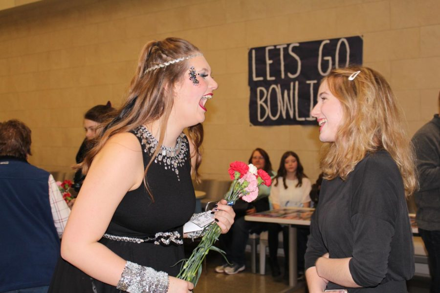 Cast member and senior Peyton Falen laughs with stage manager and junior Summer Sperke, while holding onto a handful of flowers and handwritten notes that the audience members had a chance to write before the show and during intermission.