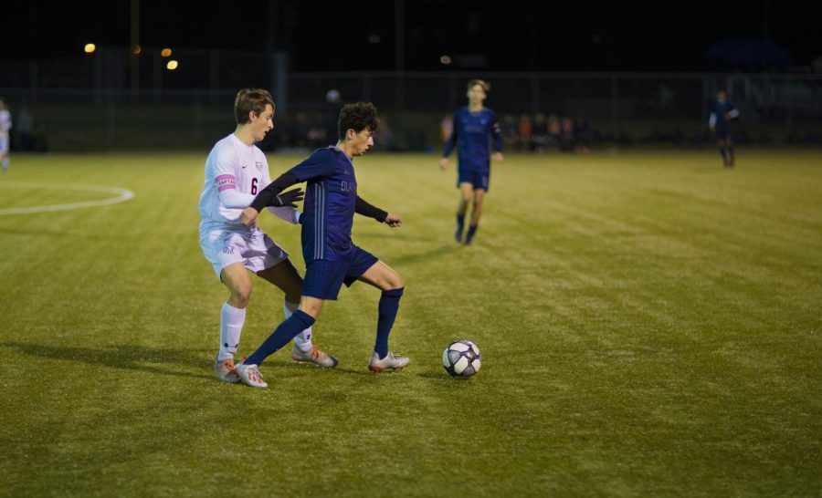 Sophomore Elyes Ellouz defends the ball from an Olathe South opponent.