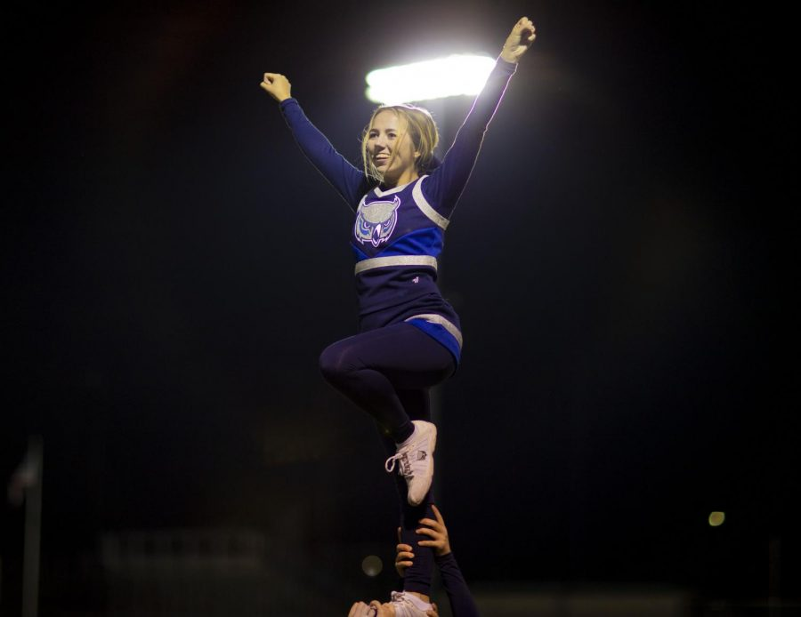 At the top of a stunt, senior Tori Schupp cheers on the sidelines of the final regional game against Olathe South.