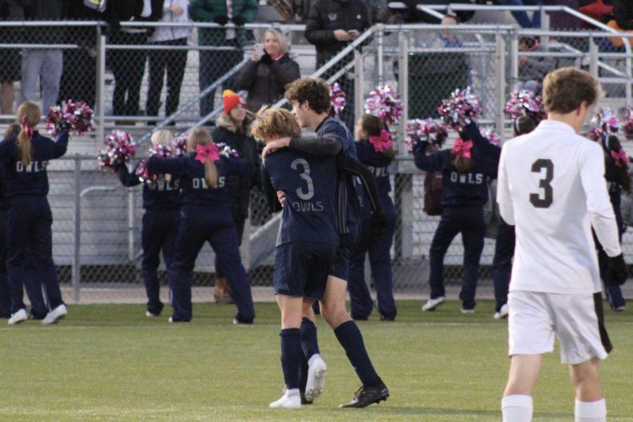 Junior Henry Curnow and senior Cameron Denton celebrate a goal made in the game against Olathe Northwest.