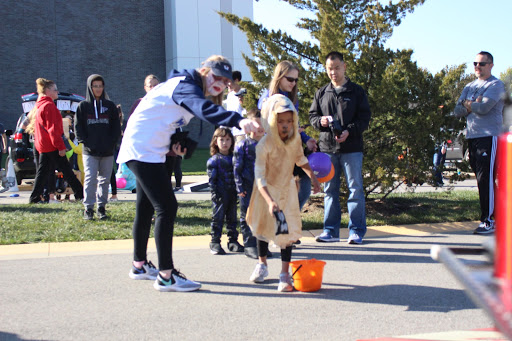 Senior Abby Marshall directs a trunk-or-treater to the cornhole board as she throws a bag at the softball trunk.