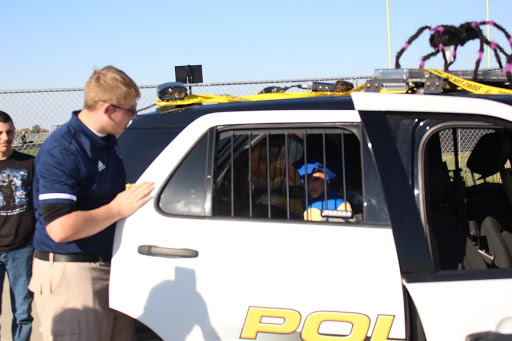 "Freshman Cooper Zwarts puts a young trunk-or-treater ""behind bars"" in the Public Safety police car. Public Safety Academy dressed up the school police car in Halloween decorations to show off for Trunk-or-Treat."