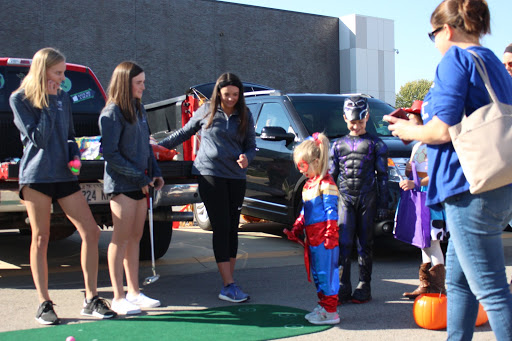 Golfers, freshman Corinne Zieg, freshman Liz Lyons and senior Bailey Basham help host the golf team trunk. The golf team put up a mini putt-putt green for the trunk-or-treaters.
