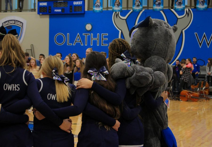 Owen the Owl and the cheerleaders of Olathe West link arms and sing the alma matter before the assemble officially begins.