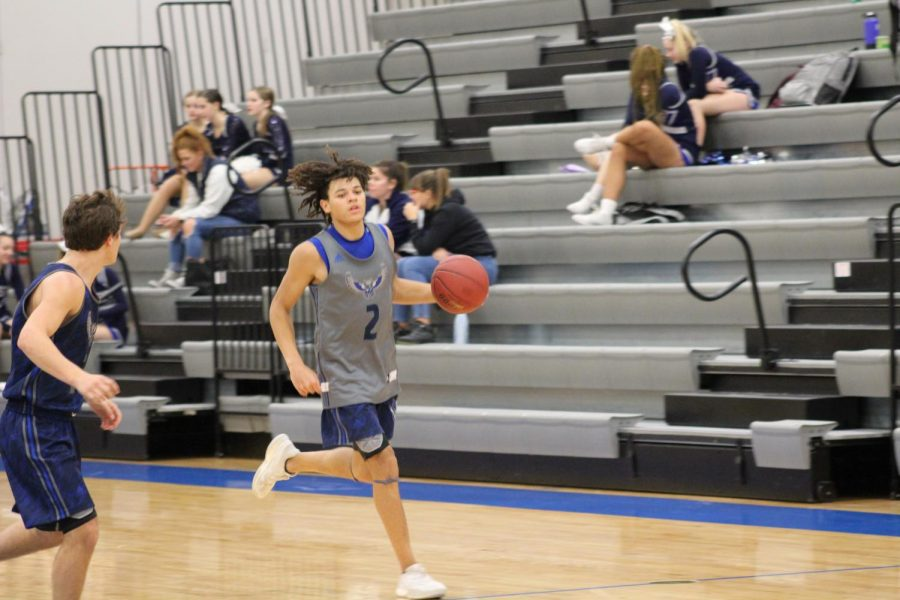 Senior Cougar Downing dribbles the ball down the court looking for an open shot.