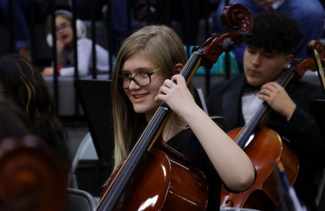 Junior Ella Powell plays the cello as family and friends of the orchestra watch.