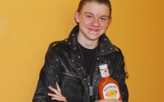 Matthew Goans poses with his signature leather jacket and a bottle of Buffalo sauce: the inspiration behind his nickname, Sssauce.