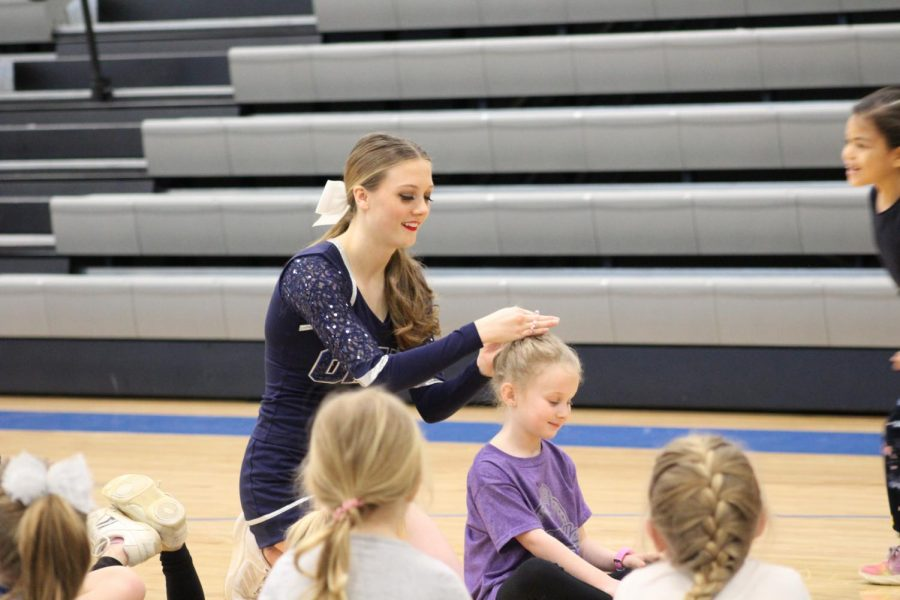 Little Owls Dance Camp: Senior Mikayla Forde helps a dancer with her hair while playing duck duck goose.