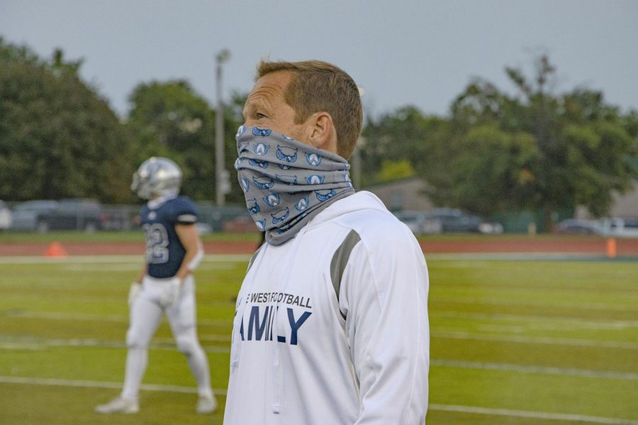 While wearing a face covering, Greg Morgan coaches the football team against Lawrence High School on September 18, 2020.