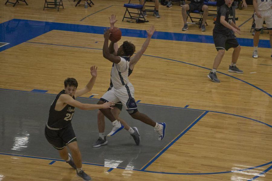 Senior Reggie Dennis gets in the lane on offence to go for a shot, just getting past two Barstow defenders.