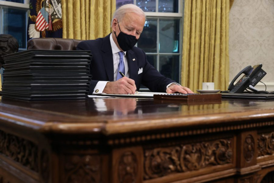 President Biden works in the oval office the day after inauguration.