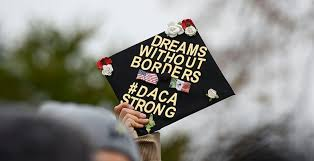 A graduated DREAMer holds their DACA-inspired hat up high.