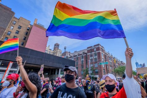 Masked people walk the streets of New York City for Pride.