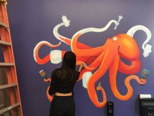 Junior Lana Young adds details to her acrylic mural of an octopus.