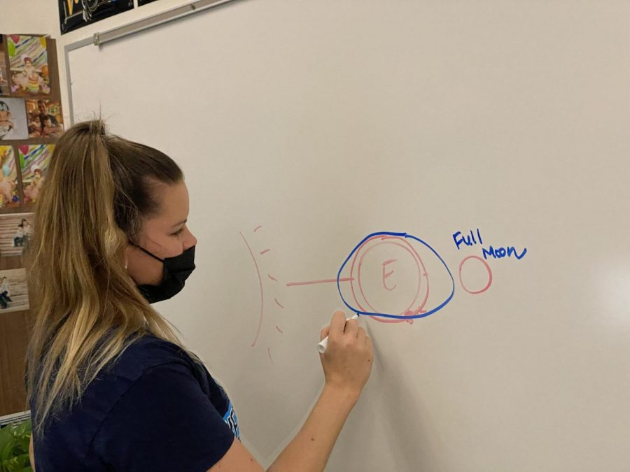 Physics and astronomy teacher Samantha Baker demonstrates the moon's effect on the tide.