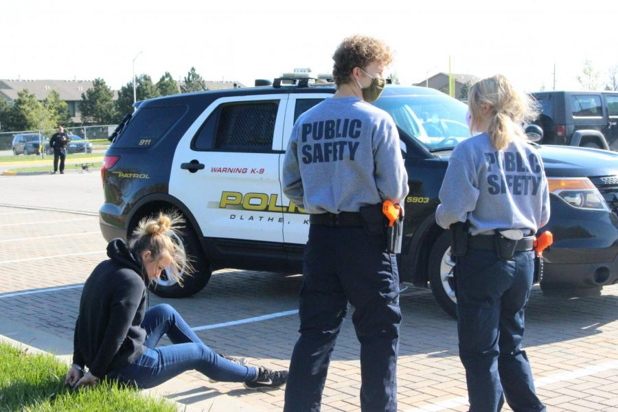 Seniors Bobby Wimpey and Summer Sperke discuss their next steps as the suspect sits hand cuffed on the curb.