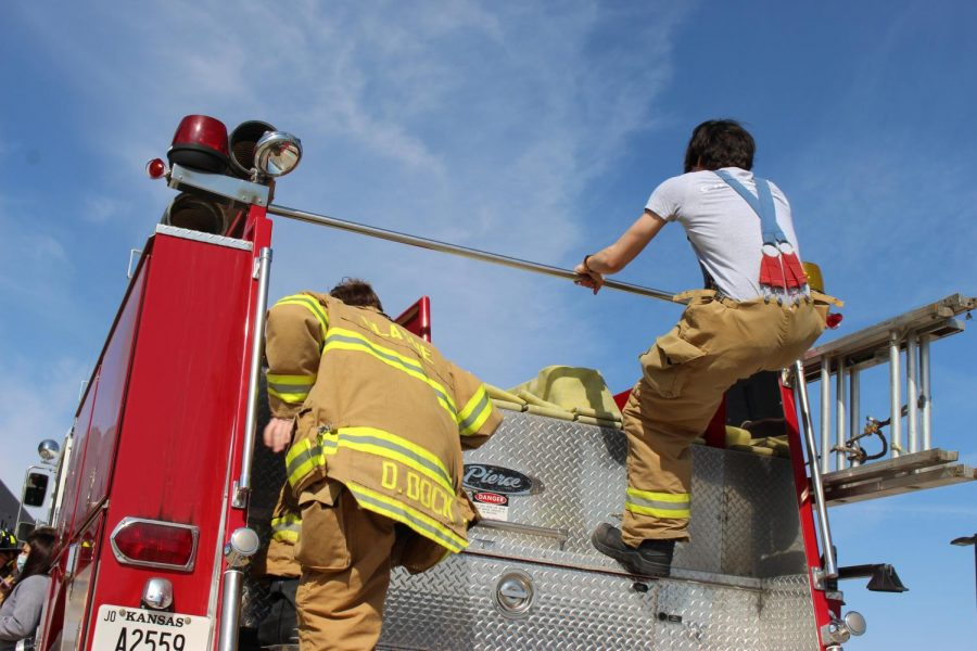 Firefighting students climb aboard the fire truck.