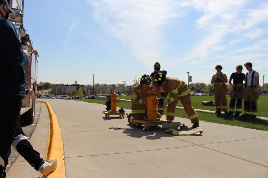 Firefighting students connect attachments to a hydrant in a race against their classmates.