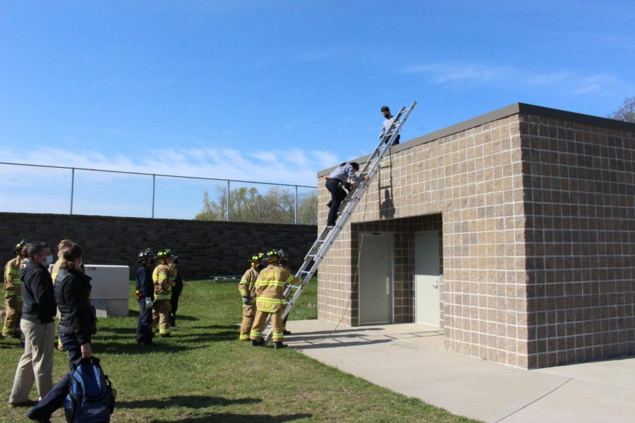 Students in the Public Safety Academy's fire team help hold the base of a ladder so that senior Ingrid Beltron can climb to the top.