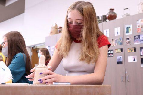Freshman Danika Davis works in art class with a mask.