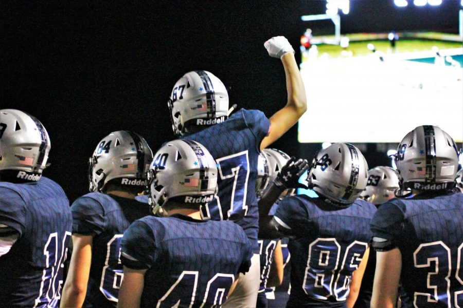 The+football+team+celebrates+their+first+home+game+win+against+Shawnee+Mission+Northwest+on+Sept.+9.+