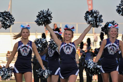 Senior Ava Schreck leads the cheerleaders as the football team runs onto the field at the beginning of the game against Shawnee Mission Northwest on Sept. 9.