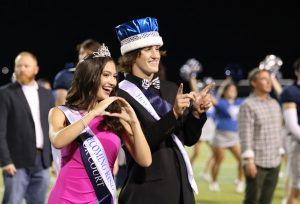 Homecoming Queen Sophie Schneider and Homecoming King Stone El-Attrache pose for photos after being announced the winners of the homecoming royalty vote at the game on Friday.