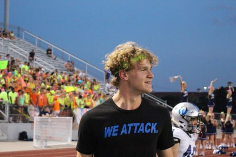 As the varsity football team plays against Shawnee Mission North, Griffin cheers on the team on the sidelines.