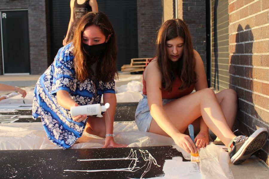 Stuco members sophomores Kolby Brown and Megan Ulrich paint city skylines for the homecoming dance decorations.